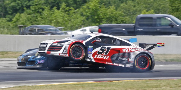 APR's Audi R8 climbs up the left side of TRG Porsche.
